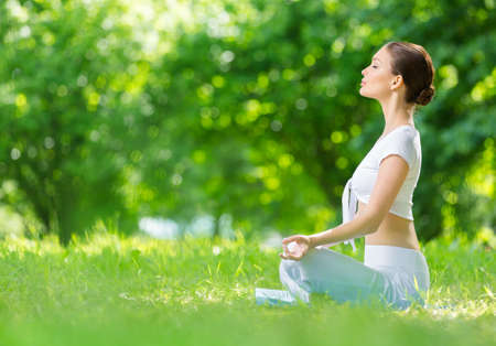 Profile of woman who sits in asana position zen gesturing. Concept of healthy lifestyle and relaxation Standard-Bild