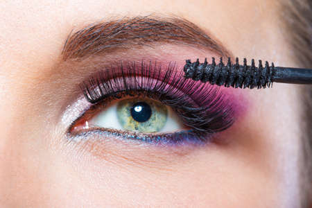 Close up of female eye with bright make-up and brush applying mascara on eyelashes photo