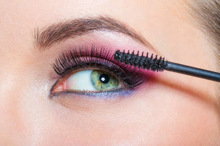 Close up of female eye with bright makeup and brush applying mascara on eyelashes photo