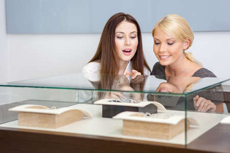 platinum hair: Two women looking at showcase with jewelry at jewelers shop. Concept of wealth and luxurious life