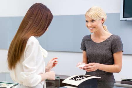 chose: Consulente aiuta signora scegliere gioielli nel negozio di gioielleria. Concetto di ricchezza e di vita di lusso Archivio Fotografico
