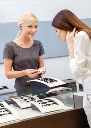 affluence: Shop assistant helps lady to choose jewelry at jewelers shop. Concept of wealth and luxurious life