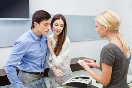Shop assistant helps couple to choose jewelry at jeweler's shop. Concept of wealth and luxurious life photo