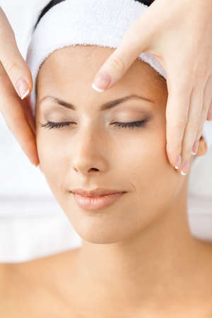 Headshot of naked woman with closed eyes getting face massage. Concept of relax and medicine photo
