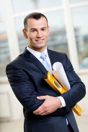Engineer wearing suit with blue tie hands layout and level photo