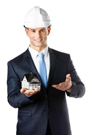 architecting: Engineer in white hard hat shows small model house, isolated on white