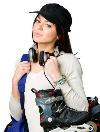 Half-length portrait of teenager handing roller skates and wearing peaked cap, blue rucksack and earphones, isolated on white photo