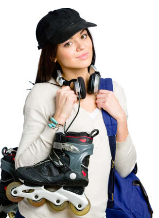 Half-length portrait of teenager keeping roller skates and wearing peaked cap, blue rucksack and earphones, isolated on white photo