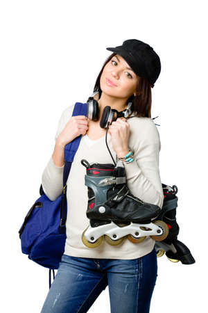 Half-length portrait of teenager holding roller skates and wearing peaked cap, blue rucksack and earphones, isolated on white photo