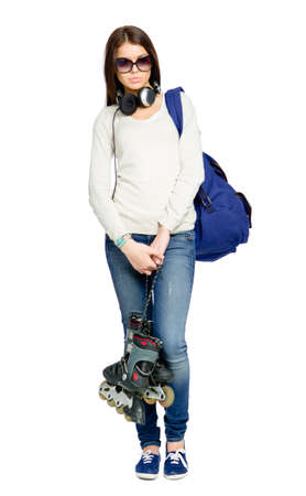 Full-length portrait of teenager with roller skates, rucksack and earphones wearing black sunglasses, isolated on white photo