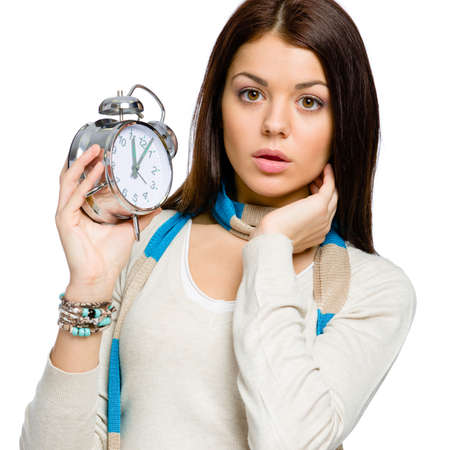 Amazed young girl with alarm clock wearing colored scarf and beige pullover, isolated on white photo