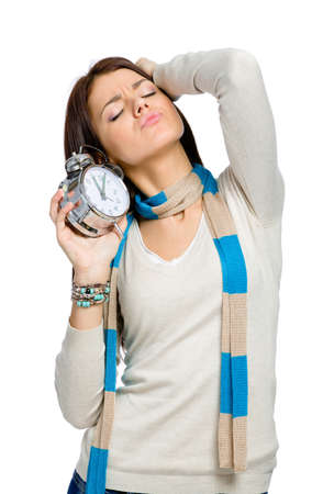 Stretching woman with alarm clock wearing colored scarf and beige pullover, isolated on white photo