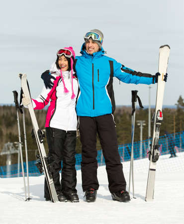 Full-length portrait of two embracing downhill skiers with skis in hands photo