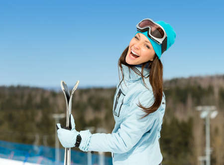 Half-length portrait of female downhill skier with skis in hands. Concept of winter sports and cute entertainment photo