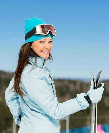 Half-length portrait of female skier with skis in hands. Concept of winter sports and cute entertainment photo