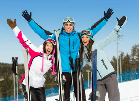 Half-length portrait of group of downhill skier friends with hands up. Concept of cute winter sport and funny vacations with friends