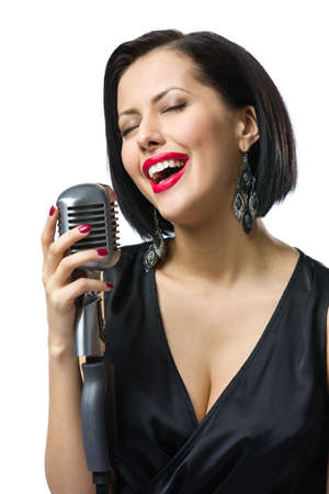Portrait of female musician with closed eyes wearing black evening dress and keeping microphone, isolated on white. Concept of music and retro fashion photo