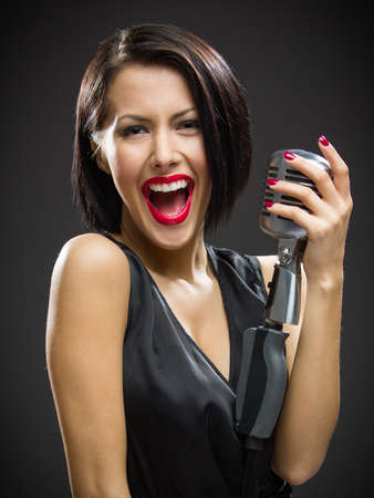 Half-length portrait of female musician wearing black evening dress and keeping mic on grey background. Concept of music and retro fashion photo