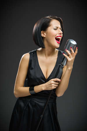Half-length portrait of female musician wearing black evening dress and handing mic on grey background. Concept of music and retro fashion photo