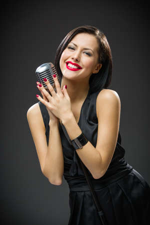 Half-length portrait of female singer wearing black evening dress and keeping mike on grey background. Concept of music and retro fashion photo
