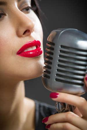 microfono antiguo: Headshot de la cantante manteniendo micrófono en el fondo. Concepto de la música y de la moda retro