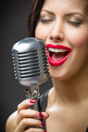 Headshot of female singer with closed eyes keeping microphone on grey background. Concept of music and retro fashion photo
