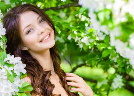 Portrait of pretty girl near the flowered tree in the park. Concept of youth and natural beauty