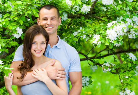 Pretty couple embracing near blossomed tree in the park. Concept of love and stable relations photo