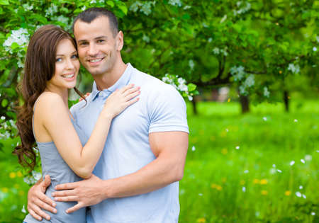 Young couple embracing near blossomed tree in the park. Concept of love and stable relations photo