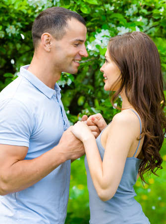 Couple joins hands and looks at each other near blossomed tree in the park. Concept of love and stable relations photo