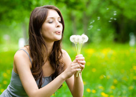 Woman blows dandelions in the park. Concept of nature and rest photo