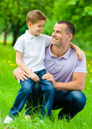 Father keeps son on the knee in the green park. Concept of happy family relations and carefree leisure time photo