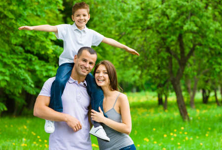Happy family of three. Father keeps son airplane gesturing on shoulders. Concept of happy family relations and carefree leisure time Stock Photo