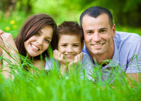 problemas familiares: Feliz familia de tres tirado en la hierba. Concepto de las relaciones familiares felices y tiempo libre sin preocupaciones