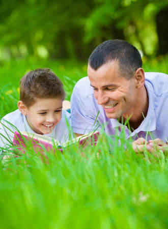 field study: Father and son read book lying on green grass in park. Concept of happy family relations and carefree leisure time Stock Photo