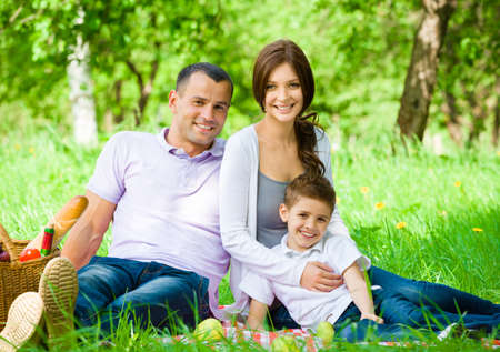 Happy family of three has picnic in green park. Concept of happy family relations and carefree leisure time photo