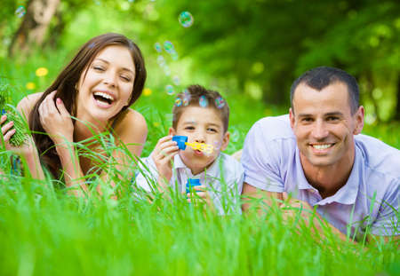 problemas familiares: Feliz familia de tres tumbado en la hierba, mientras que el hijo sopla burbujas. Concepto de las relaciones familiares felices y tiempo libre sin preocupaciones