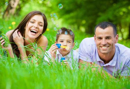 Gelukkig gezin van drie liggend op het gras terwijl zoon blaast bellen. Concept van de gelukkige familie relaties en zorgeloze vrije tijd