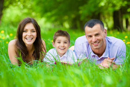 Happy family of three lying on grass while reading book. Concept of happy family relations and carefree leisure time photo