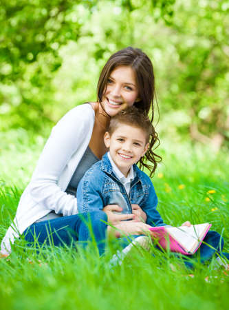 Mom and son with book sitting on green grass in park. Concept of happy family relations and carefree leisure time photo
