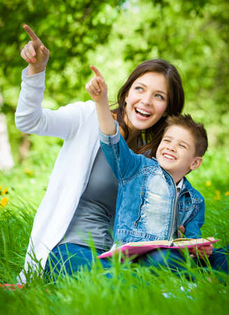 Mother and son with book sitting on green grass pointing hand gesture in park. Concept of happy family relations and carefree leisure time photo
