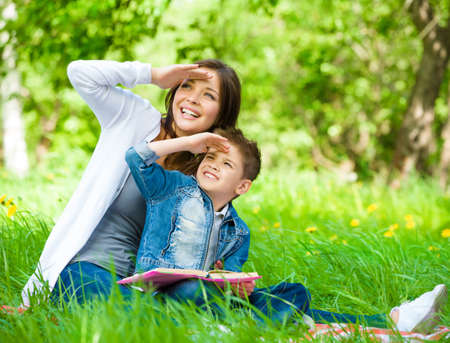 Mother and son with book sitting on green grass cover eyes from sun in park. Concept of happy family relations and carefree leisure time photo