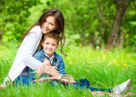 Mom and son with book sitting on green grass in green park. Concept of happy family relations and carefree leisure time photo