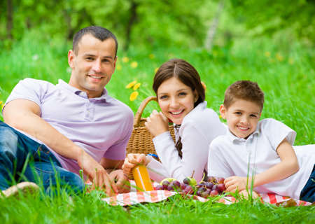 Happy family of three has picnic in park. Concept of happy family relations and carefree leisure time photo