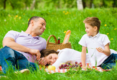Family of three has picnic in green park. Concept of happy family relations and carefree leisure time