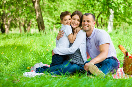 Family of three has picnic in park. Concept of happy family relations and carefree leisure time photo