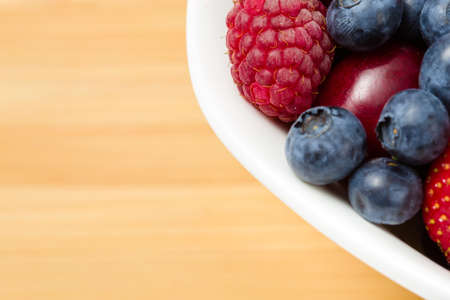 Close up view of part of plate full of berries on the table. Concept of healthy eating and dieting lifestyle photo