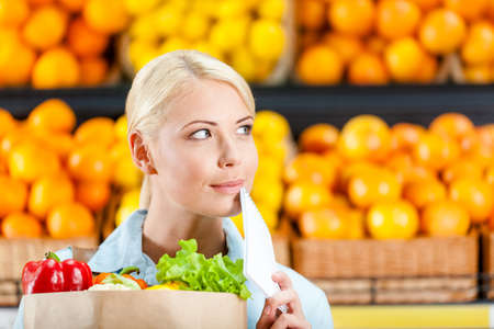 Reading list of products girl hands bag with fresh vegetables against the shelves of fruits in the shopping mall photo
