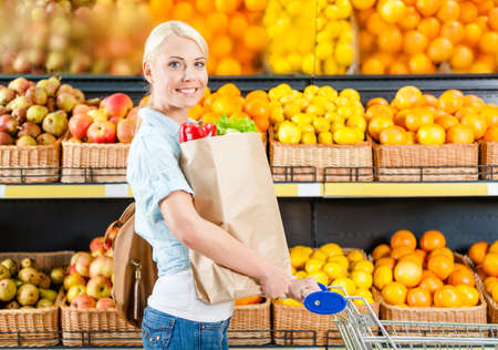 food package: Girl with cart hands bag with fresh vegetables against the shelves of fruits in the market