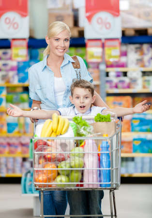 Mother and son whose arms are outstretched keeps cart full of products in shop. Concept of healthy food and consumerism photo